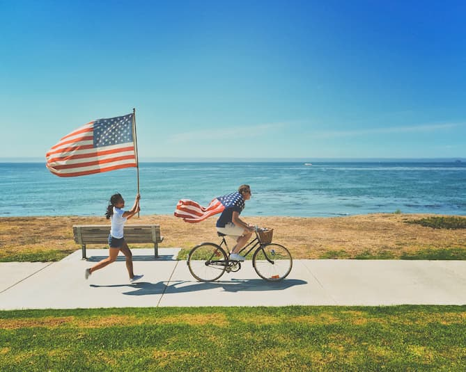 Photo of two people carrying American flags.