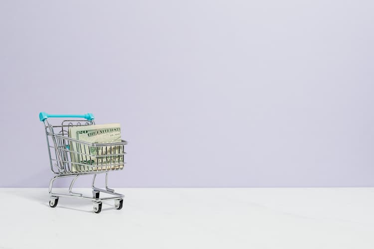 Photo of a shopping cart full of money.